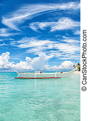 Boat on a tropical island with turquiose waters