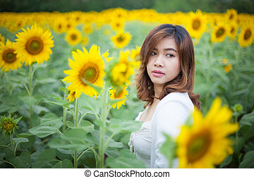 Young asian woman in sunflower field