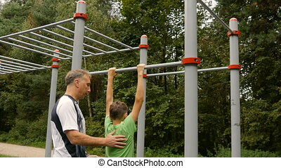Dad teaches his son to do pull-ups, on the sportground,...