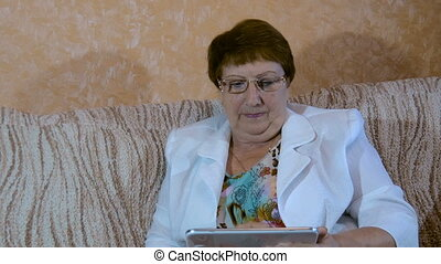 Elderly woman studying tablet