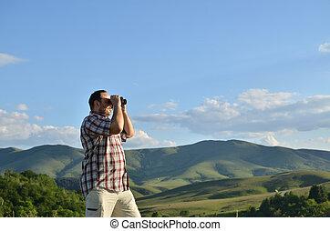 Man Exploring Nature through Binoculars - Man is using...