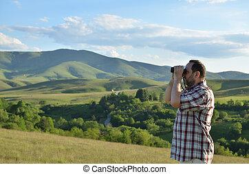 Man Watching Landscape through Binoculars - Man is using...