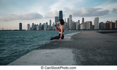 Runner athlete sitting on the background of skyscrapers and seaside