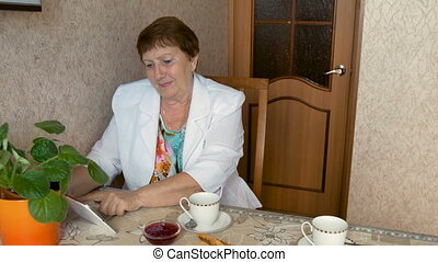 An adult woman using a tablet, drinking tea at the table.