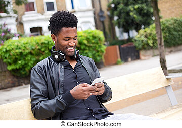 text messages - young man reading his text messages sat on a...