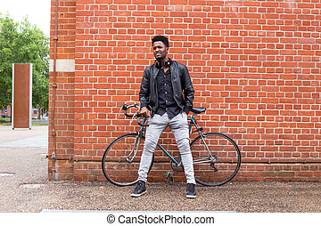 man and his bike - young man with his bike leaning against a...
