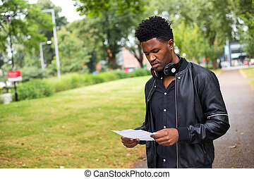 man reading a letter - young man reading a letter outdoors