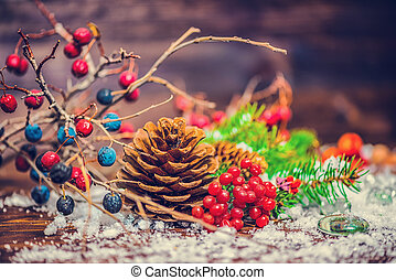 Thanksgiving holiday greeting card with autumn fruit, apple, nuts, cones, berries, fir tree and snow, toned style, close up