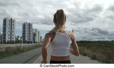 Girl with blond hair jogging rear view