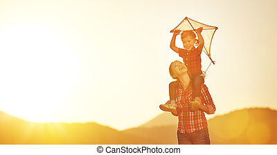 happy family mother and child run on meadow with a kite in summer