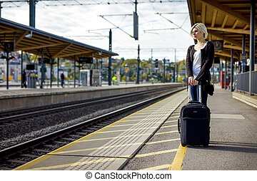 Woman With Luggage Waiting On Platform Of Railroad Station -...