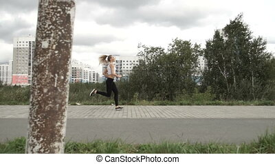 Girl is running on the background of houses