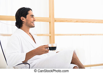 Carefree guy relaxing with hot drink - Happy young man is...