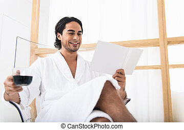 Joyful guy in bathrobe with magazine - Relaxed young man is...