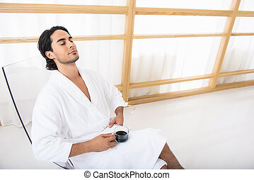 Relaxed guy with hot drink on vacation - Young man is...