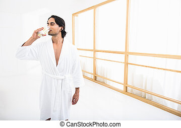 Relaxed guy is thirsty after bathing - Young man is drinking...