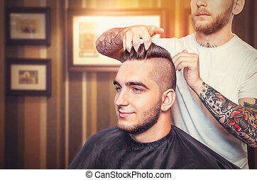 Young man having hair dress, barber fingers in the hair