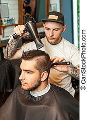 Young man having hair dress, barber working with hair dryer
