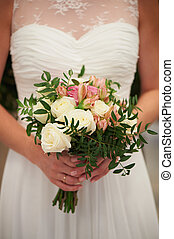 Wedding bouquet in hands of bride. Delicate colours. White, cream, rose