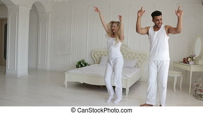 Couple dancing bedroom, mix race man woman playing having fun together
