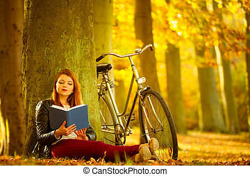 Lady reading under tree - Relax intellectual cycling fitness...