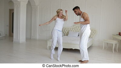 Couple dancing bedroom, mix race man woman playing having...