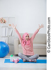 woman with hijab doing exercise at home