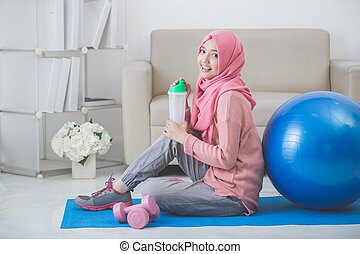 woman with hijab doing exercise at home - healthy asian...