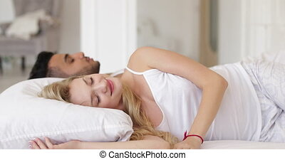 Woman turning off alarm clock cell phone lying in bed couple morning wake up smile