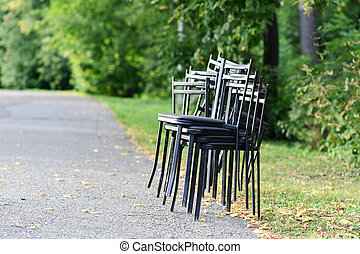 Metal chairs stacked on the side of the road