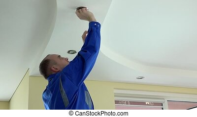 man unscrew halogen bulb for replacing - man in blue uniform...