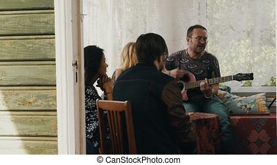 Company of friends relax at table on terrace of country house. Man play guitar