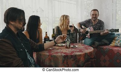 Friends resting in country house at table with drinks. Man playing guitar sing