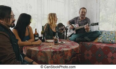 Friends resting in country house at table drink alcohol listen man play guitar