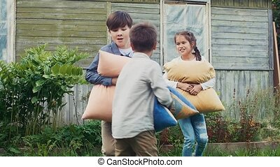 Two boys and girl fight pillows in yard of country house. Countryside. Childhood