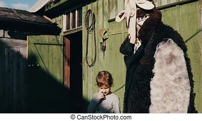 Man in creepy costume take hand of girl at old barn in countryside. Sunny day