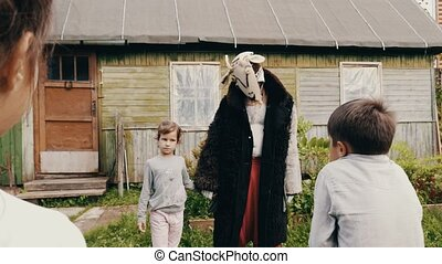 Man in creepy cow costume walk with girl in countryside. Man...