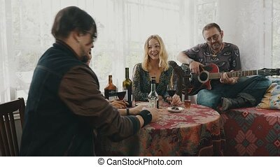Friends on terrace of country house at table drink alcohol. Man playing guitar