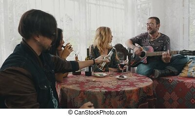Friends relax in country house at table drink alcohol. Man playing guitar. Fun
