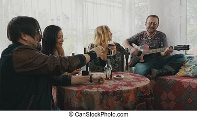 Friends resting in country house at table drink alcohol. Man play guitar. Cheer