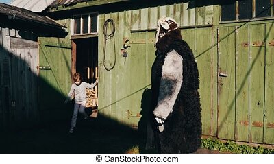 Girl walk out from old barn in countryside. Man in creepy costume touch her head