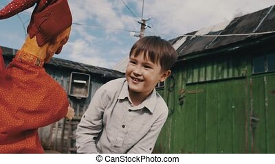 Toy doll in orange suit play with boy in countryside. Puppet...