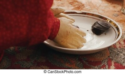 Toy doll take big chocolate candy from plate by wooden...