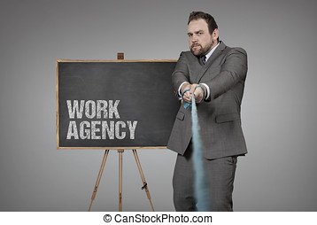 Work agency blackboard with businessman pulling rope at...