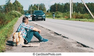 Man with backpack sit at road in countryside. Hitchhiking. Waiting. Smartphone