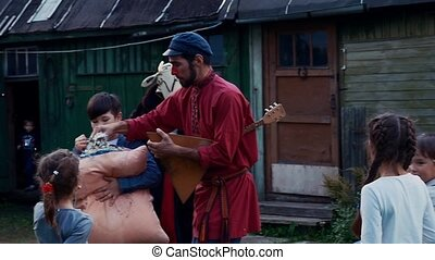 Man with balalaika give man feathers from pillow in yard of country house. Kids