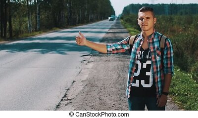 Young man with backpack hitchhiking at road in countryside. Thumb up. Sunny day