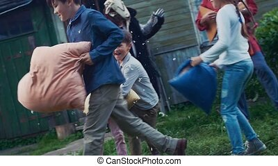 Kids fight pillows in yard of country house. Flying feathers. Men in costumes