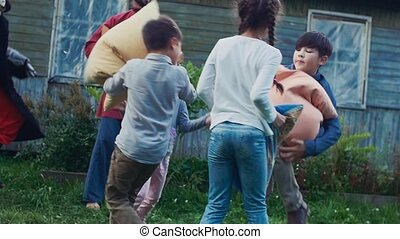 Children fight pillows in yard of country house. Flying feathers. Men in costume
