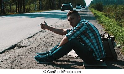 Man sit at road in countryside. Hitchhiking. Thumb up. Smoking cigarette.